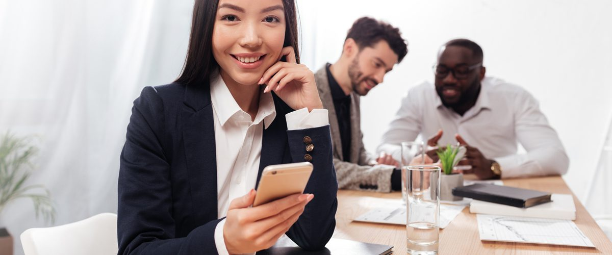 Portrait of beautiful asian businesswoman sitting in office and joyfully looking in camera with cellphone in hands and multinational business partners on background